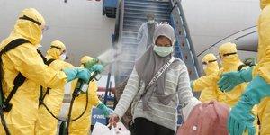 Coronavirus / Covid-19 : Des médecins diffusent un spray antiseptique sur une femme rapatriée de Chine en Indonésie, le 2 février 2020