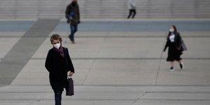 Coronavirus : une femme portant un masque marche dans le quartier La Défense à Paris