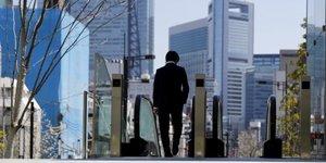 Un salarié japonais marche seul devant un escalator